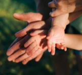 Drie paar handen van ouders en kind